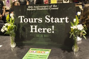 "A sign on a desk that reads ""Tours start here""."