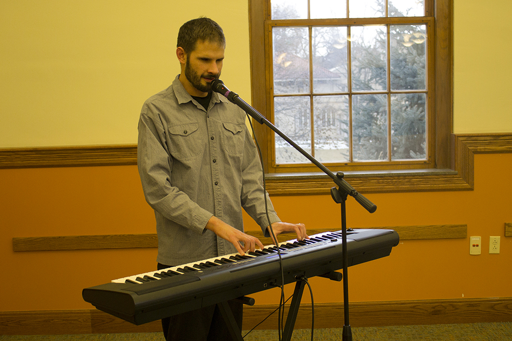 A man plays a keyboard and sings into a microphone.