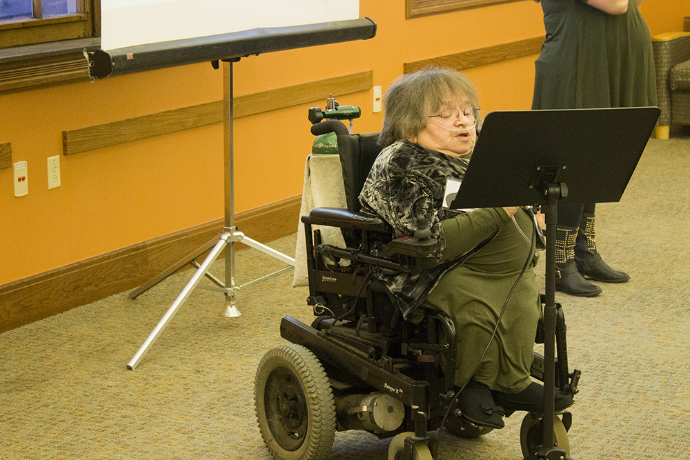 A woman in a wheelchair reads from a podium while talking into a microphone.