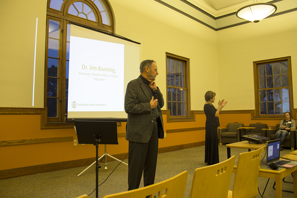 A man stands talking into a microphone while a sign language interpreter stands interpreting in the background.