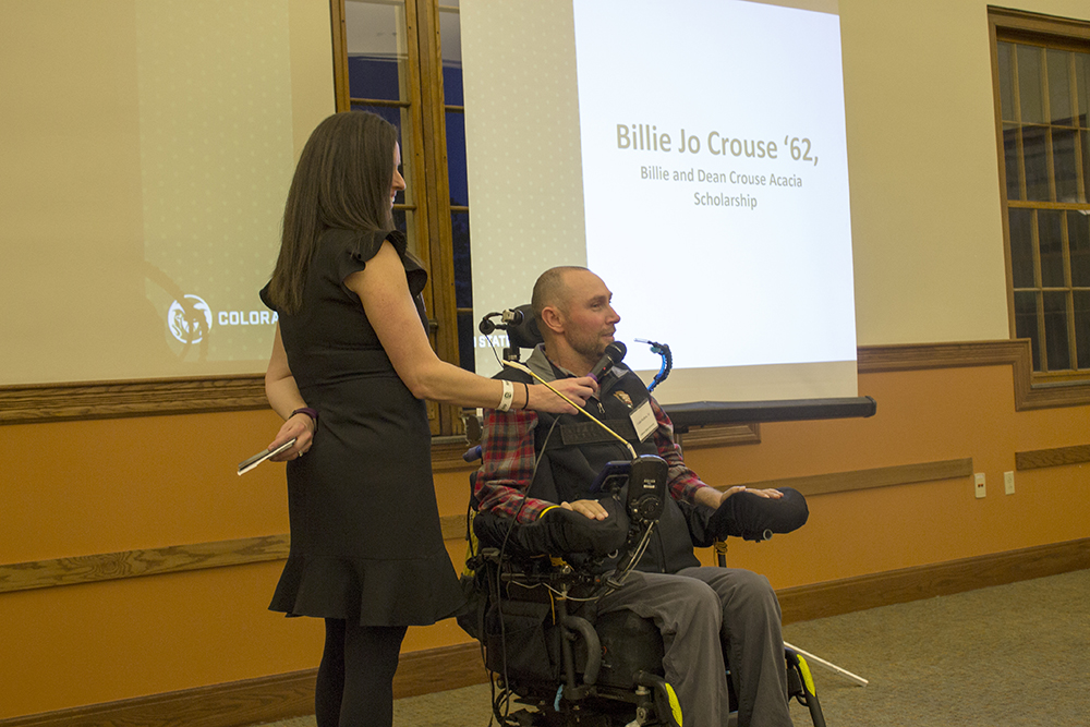 A man in a wheelchair talks into a microphone that a woman holds for him.